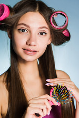 attractive young girl makes a fashionable hairstyle with curlers and combs