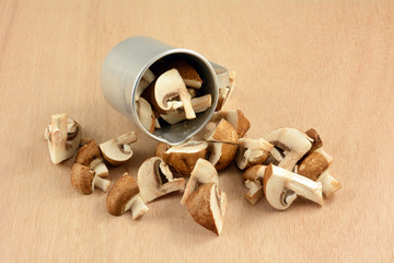 Quartered baby portabello mushrooms spilling out of retro vintage \metal measuring cup onto wooden table