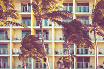 Tropical hotel exterior with balconies and palm trees swaying in the breeze  Fototapete