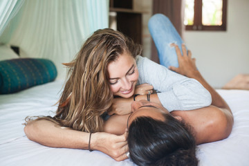 young attractive smiling man and woman are lying on the bed and hugging.
