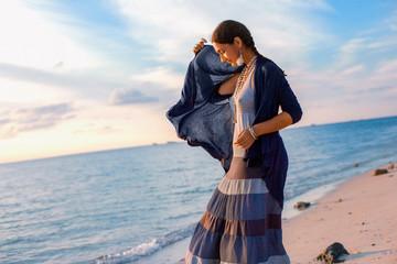Beuatiful young boho woman walking on the beach at sunset