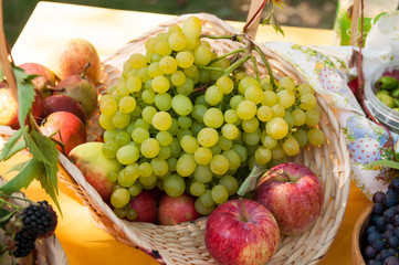 In basket, apples and grapes, autumn harvest