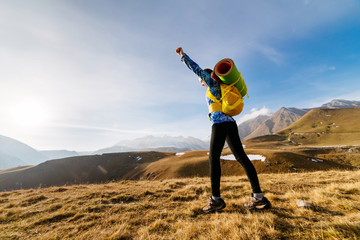 active sports girl raised her hand up, travels along the Caucasian ridge with a backpack and a tent