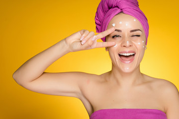 Laughing beautiful girl shows two fingers, wearing a pink towel, applied cream on face