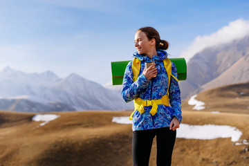 smiling young girl travels through the Caucasian mountains with a backpack and tent