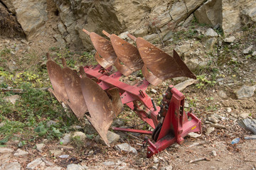 Rusty blades of farm equipment in a forest
