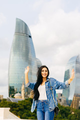 smiling happy girl raised her hands up, enjoys vacations in Baku