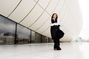 stylish woman in a black suit and white shirt posing against the background of an unusual modern building in the city of Baku