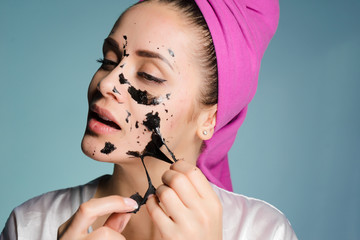 an attractive girl with a pink towel on her head removes the black cleansing mask from her face