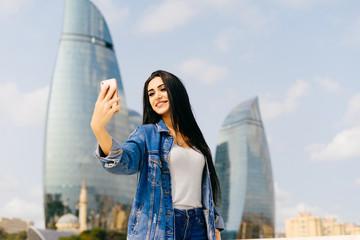 black-haired girl travels through Azerbaijan, makes selfie against the background of modern buildings in Baku
