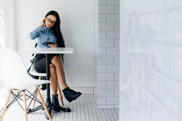 young smart girl freelancer in glasses works on a tablet in a cafe, next to the window