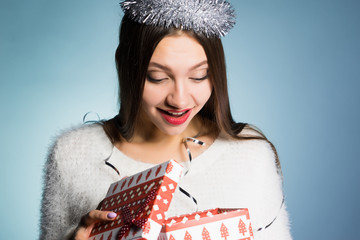 happy young girl received a gift for the new year, looks in the gift box