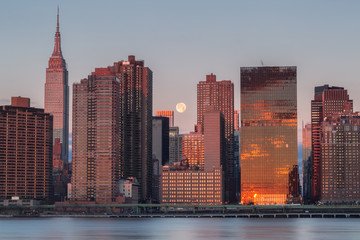 View on Manhattan with full moon from east river at sunrise