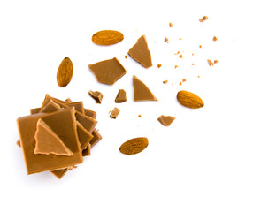 pieces of milk chocolate and crumbs and almonds nuts on white background