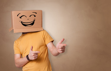 Young man with happy face illustrated cardboard box on his head