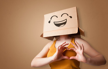Funny woman wearing cardboard box on her head with smiley face