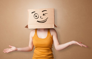 Pretty woman standing and gesturing with a carton box on her head