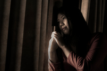 dramatic portrait of young sad and depressed Asian Chinese woman crying desperate broken heart suffering depression and anxiety in dark light at home curtains window