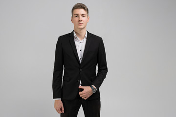 Portrait of young man in black suit isolated on white background