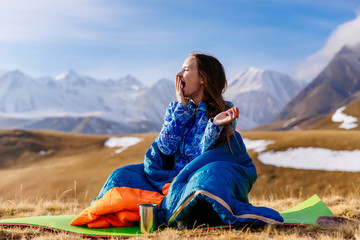 a young girl loves to travel, sits in a sleeping bag on the ground, yawns, against the background of the Caucasian ridge