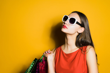 beautiful young girl in sunglasses loves shopping, bought a lot of things, in a black penny