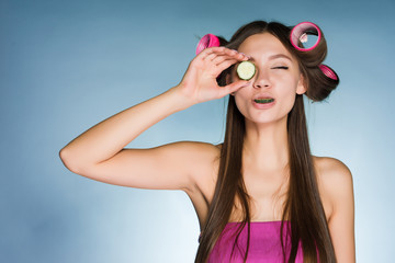 a funny young girl is going to a party, on the head of a curler, keeps pieces of cucumber in her hand and in her mouth for moisturizing the skin