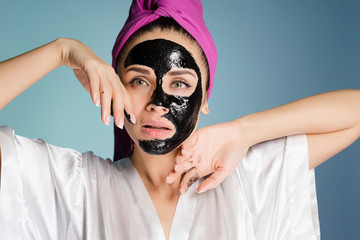 beautiful young girl with a pink towel on her head, on her face a black cleansing mask