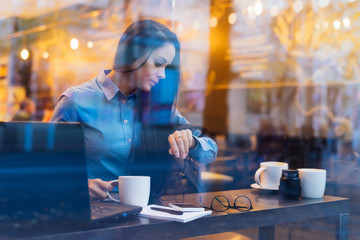 brunette girl freelancer working in a cafe on a laptop looking at a wristwatch