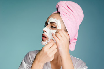 beautiful young girl with a pink towel on her head removes a white nourishing mask from her face