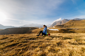 active young traveler engaged in yoga against the background of the Caucasus mountains, enjoys nature