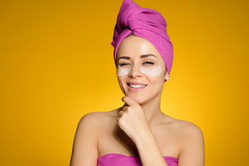 smiling attractive girl with a pink towel on her head, under the eyes of silicone patches
