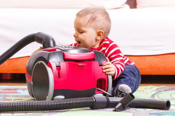 Baby boy on carpet at home and vacuum cleaner with accessories