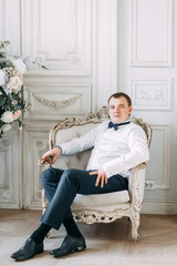 The preparations of the groom in a Deluxe hotel. the man in the shirt and jacket.