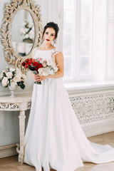 Bride in a bright Studio with a bouquet. Wedding dress and mirror.