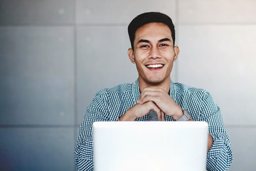 Happy Young Asian Businessman Working on Computer Laptop in his Workplace. Hands on Chin, Smiling and looking at Camera