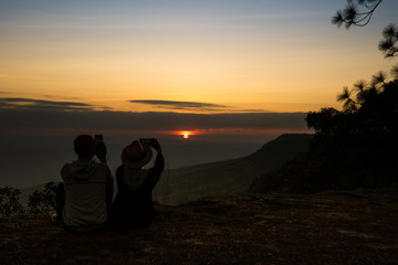 Image of sunset or sunrise on orange and yellow horizon with a silhouette of a couple in natural surrounding