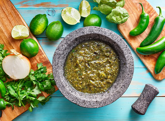 salsa verde in stone molcajete flat lay composition
