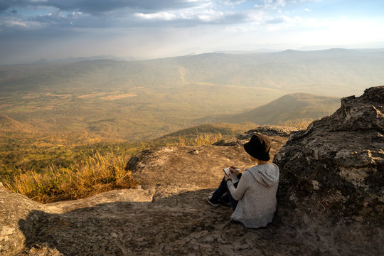 A woman sitting reading and writing looking out at beautiful natural view