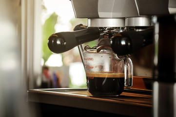 Fresh coffee in glass from professional coffee machine with filter