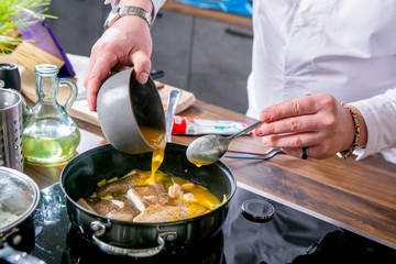 Chef adds sauce to the pan with halibut. Master class in the kitchen. The process of cooking. Step by step. Tutorial. Close-up