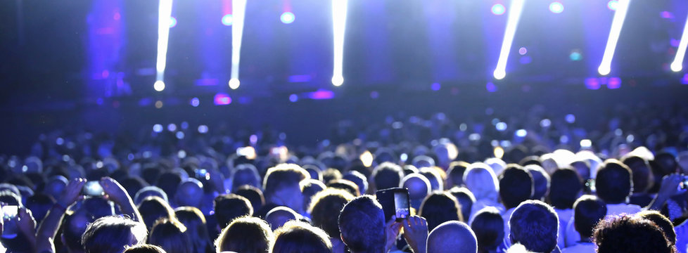 people at live concert with  spotlights on the stage