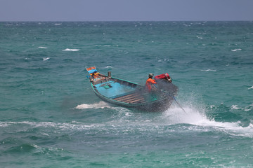 Asian men are driving the long tail boat in the sea, while a strong wind and the waves