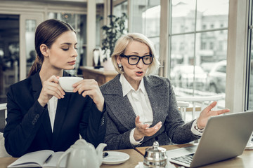 Mother and daughter having meeting in cafeteria about family business