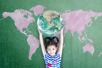 Happy Asian girl child student raising globe on school chalkboard for world literacy and gender equality concept. Elements of this image furnished by NASA...