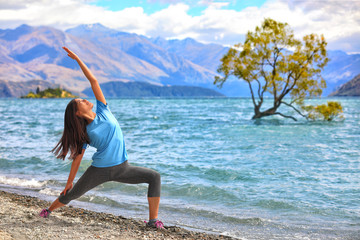 Yoga travel New Zealand. Asian girl practicing yoga at the lone tree in Wanaka lake, NZ. Woman training fitness for a healthy body and mind, meditating in the summer outdoor.