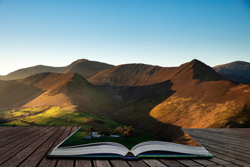 Beautiful Autumn Fall landscape image of sun beams lighting up small area of mountain side in Lake District coming out of pages of open story book