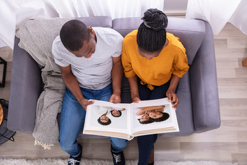 High Angle View Of A Couple Looking At Photo Album