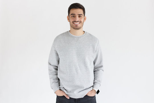 Young man in oversized sweatshirt, isolated on gray background