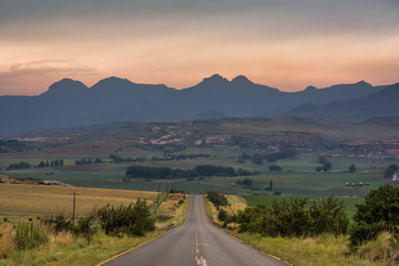 A road leading towards the Drakensberg mountains at sunrise near Clarens, South Africa