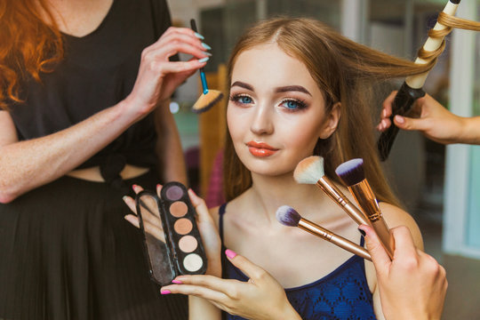 Portrait of the cheerful young woman who is sitting indoors and makeup artist doing makeup her and hairdresser doing the hairdo her